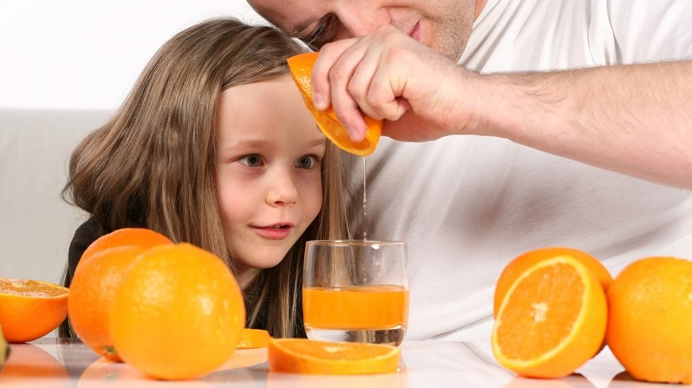 Father and daughter squeezing orange into glass