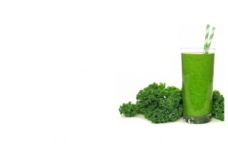 Green juice in glass surrounded by kale
