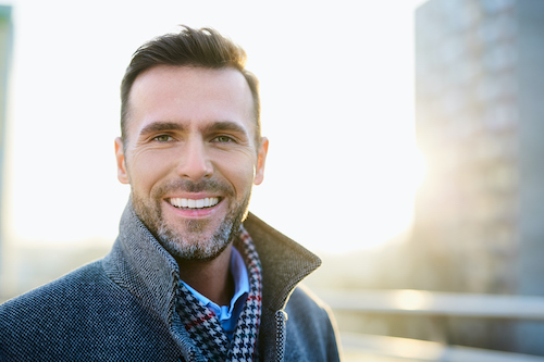 Man in collared jacket smiling downtown
